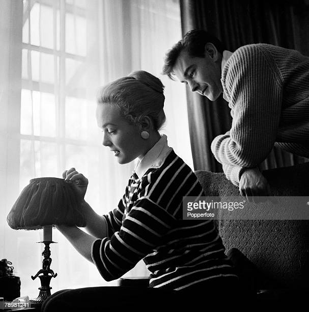 England British film and movie actress Shirley Eaton adjusts a lamp shade in her house while her fiancee Colin LentonRowe watches her