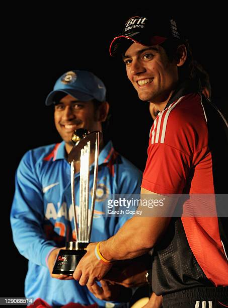 England captain Alastair Cook alongside India captain MS Dhoni hold the One Day International series trophy at a press conference at the team hotel...