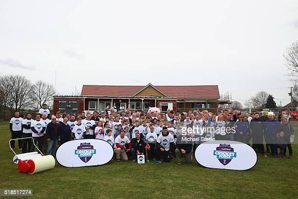 England captain Alastair Cook and ex England captain Mike Gatting pose alongside locals in front of the old and new club house during the NatWest...