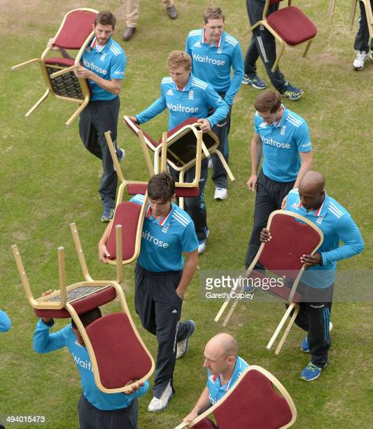 England captain Alastair Cook and the rest of his team carry back their chairs after a team photo before a nets session at Old Trafford on May 27,...