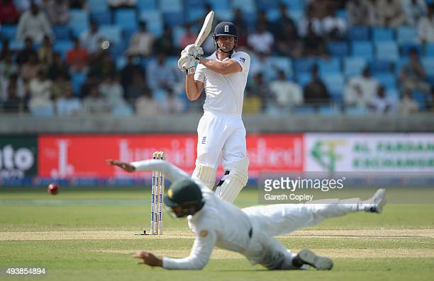 England captain Alastair Cook hits past Shan Masood of Pakistan during day two of the 2nd test match between Pakistan and England at Dubai Cricket...