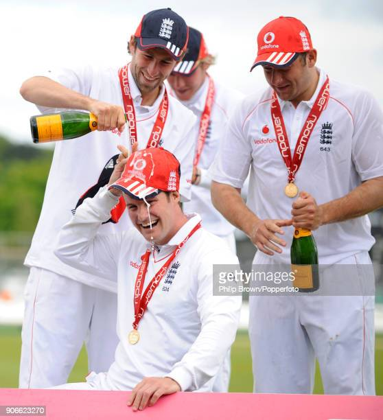 England captain Andrew Strauss has champagne poured over his head by teammate Graham Onions as Tim Bresnan waits for his turn during the presentation...
