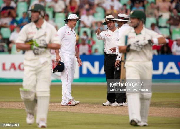 England captain Andrew Strauss talks to the umpires as South Africa's AB deVilliers and Mark Boucher leave for bad light during the second Test at...