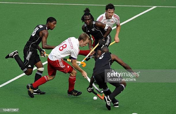 England captain Barry Middleton fights for the ball with Trinidad and Tobago players during their field hockey match at the Major Dhyan Chand...