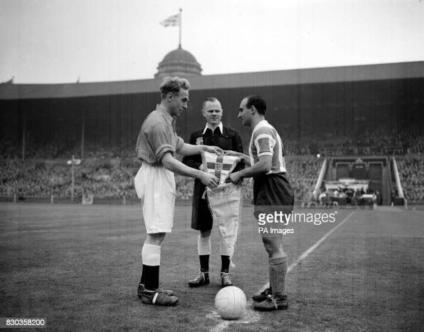 England captain Billy Wright exchanges pennants with Argentina captain Nebertol Yacono whilst referee OM Griffiths looks on before the kickoff of the...