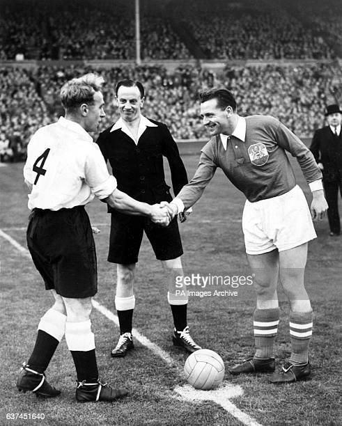 England captain Billy Wright shakes hands with Austria captain Leopold Gernhardt before the match watched by referee Jack Mowat