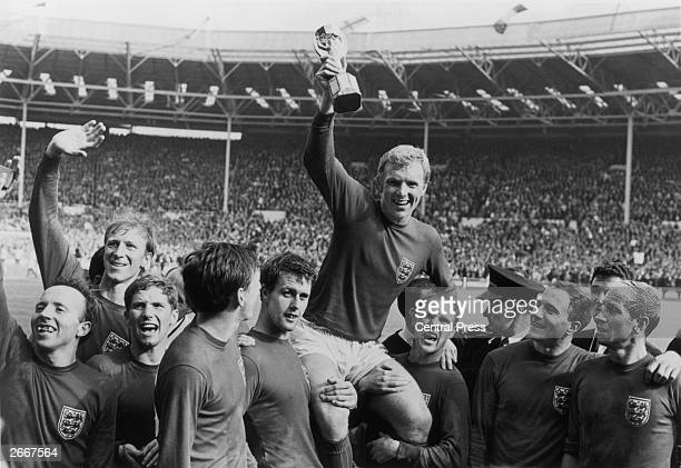 England captain Bobby Moore holds up the Jules Rimet trophy as he is carried on the shoulders of his team-mates after their 4-2 victory over West...