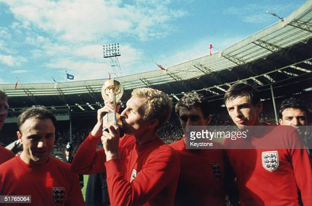 England captain Bobby Moore kissing the Jules Rimet trophy as the team celebrate winning the 1966 World Cup final against Germany at Wembley Stadium....