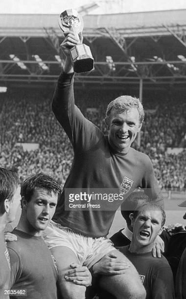 England captain Bobby Moore raises the Jules Rimet trophy in the air as he is carried on teammates Geoff Hurst and Ray Wilson's shoulders following...