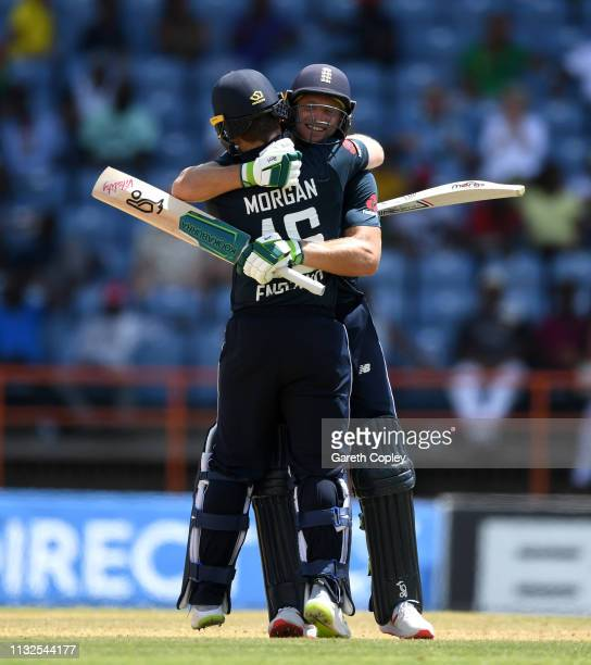 England captain Eoin Morgan celebrates reaching his century with Jos Buttler during the 4th One Day International match between the West Indies and...