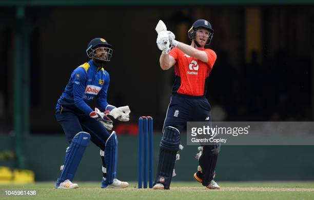 England captain Eoin Morgan hits out for six runs watched by Sri Lanka Cricket Board XI wicketkeeper Dinesh ChandimalÊduring the tour match between...