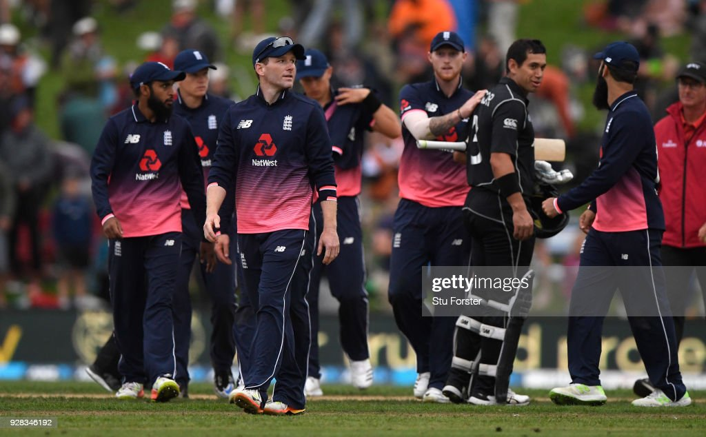 England captain Eoin Morgan leaves the field as New Zealand batsman Ross Taylor is congratulated after New Zealand win the match by 5 wickets during the 4th ODI between New Zealand and England at University of Otago Oval on March 7, 2018 in Dunedin, New Zealand.