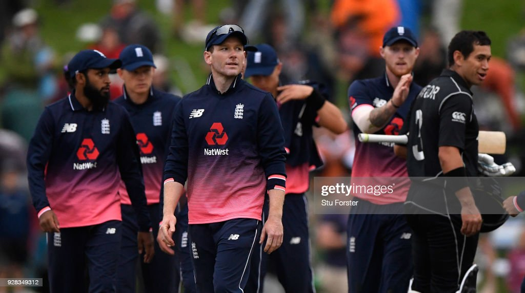 England captain Eoin Morgan leaves the field as New Zealand batsman Ross Taylor is congratulated by Ben Stokes after New Zealand win the match by 5 wickets during the 4th ODI between New Zealand and England at University of Otago Oval on March 7, 2018 in Dunedin, New Zealand.