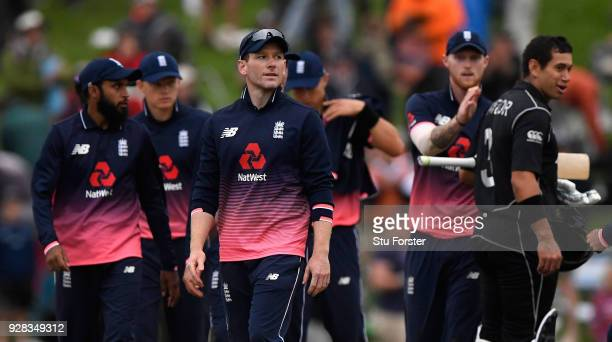 England captain Eoin Morgan leaves the field as New Zealand batsman Ross Taylor is congratulated by Ben Stokes after New Zealand win the match by 5...