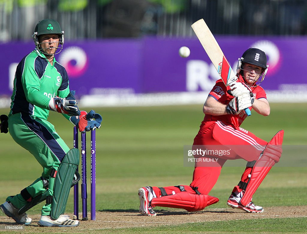England captain Eoin Morgan (R) plays a shot as Ireland wicketkeeper Gary Wilson (L) looks on during a One Day International (ODI) cricket match between Ireland and England at Malahide Cricket Club in Malahide, Ireland, on September 3, 2013.