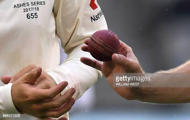 England captain Joe Root and bowler Chris Woakes inspect the wet ball on the fourth day of the fourth Ashes cricket Test match at the MCG in...