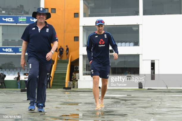England captain Joe Root and coach Trevor Bayliss head out to the wicket over the water laden covers before England Cricket Nets at Galle...