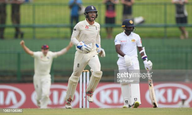 England captain Joe Root and wicketkeeper Ben Foakes celebrate after Jack Leach had taken the final Sri Lanka wicket of Malinda Pushpakumara during...