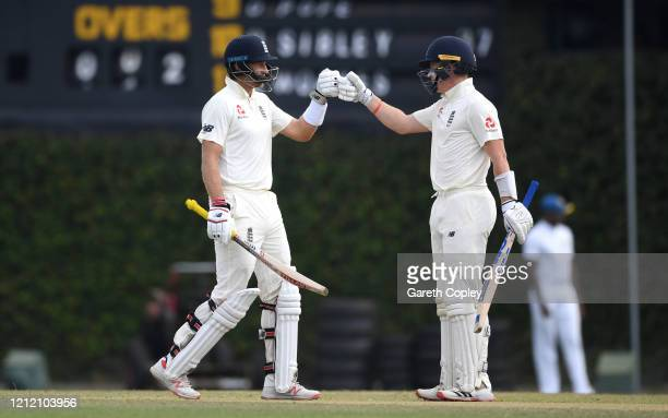 England captain Joe Root celebrates reaching his century with Ollie Pope during the tour match between SLC Board President's XI and England at P Sara...