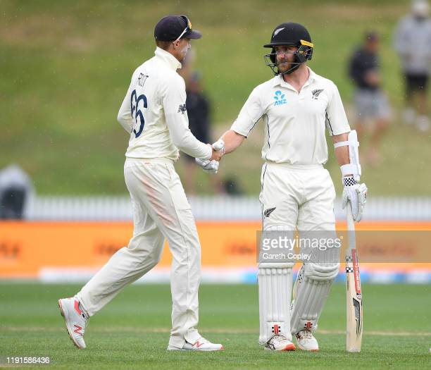England captain Joe Root shakes hands with New Zealand captain Kane Williamson as rain stops play during day 5 of the second Test match between New...