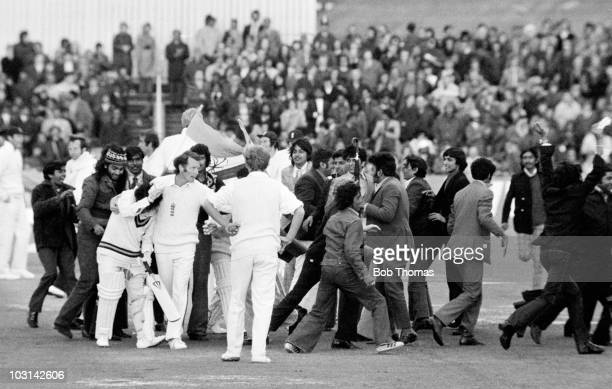 England captain Mike Denness shields Sunil Gavaskar of India from celebrating Indian fans after Gavaskar had completed his century on the third day...