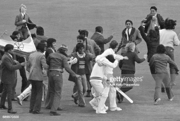 England captain Mike Denness tries to protect Indian batsman Sunil Gavaskar from spectators running onto the pitch to celebrate his century during...