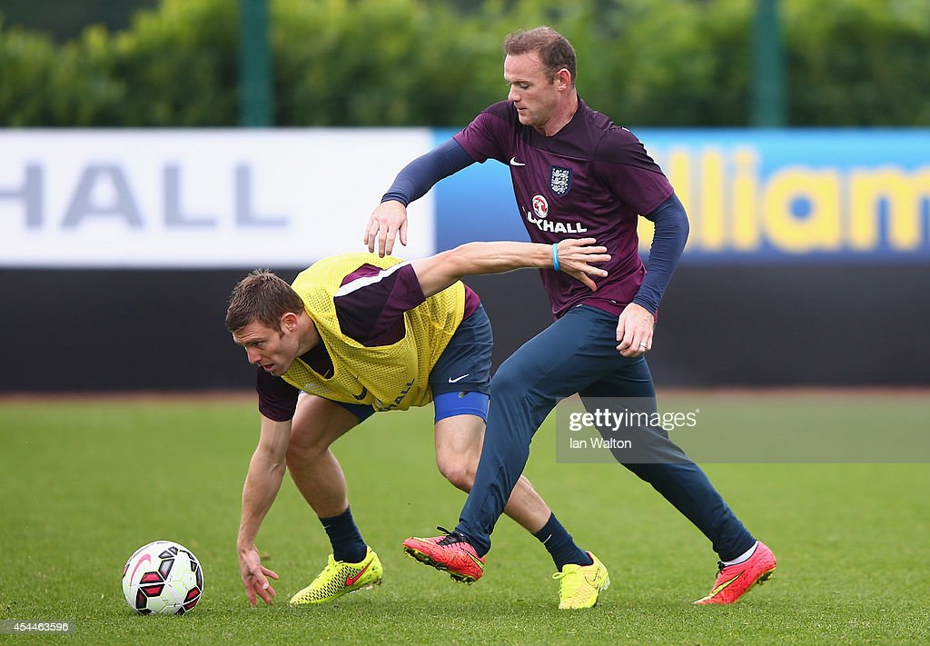 England captain Wayne Rooney tackles James Milner during a England training session before the international friendly match against Norway at London Colney on September 1, 2014 in London, England.