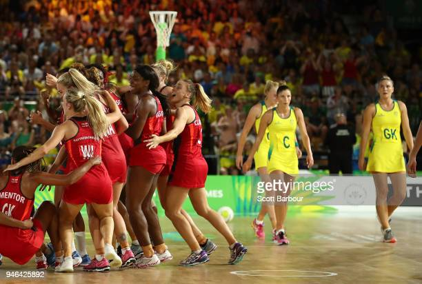 England celebrate at full time and winning as Australia look dejected as they leave the court during the Netball Gold Medal Match between England and...