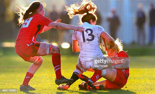 England centre Abigail Brown is tackled by Jenny Hawkins and captain Rachel Taylor during the Six Nations championship match between Wales and...