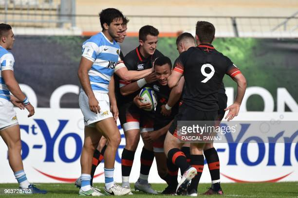 England centre Jordan Olowofela celebrates with his teammates after scoring a try during the U20 World Rugby Championship match between England and...
