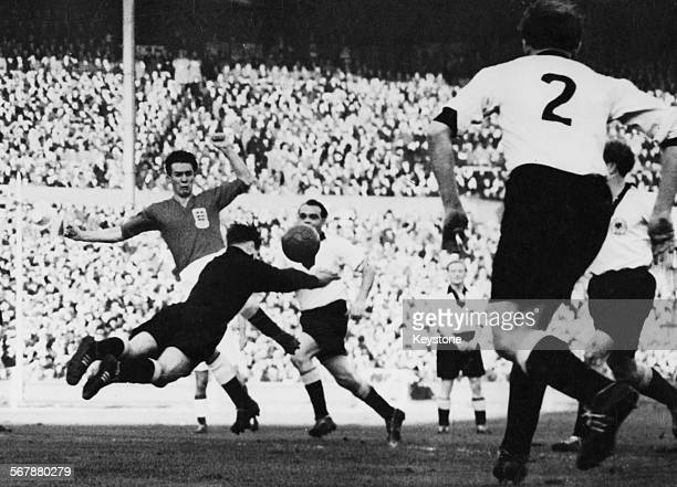 England centreforward Ronnie Allen and Germany goalkeeper Fritz Herkenrath duel for possession of the ball seconds after a free kick is awarded to...