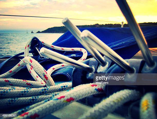 England, Channel Islands, Jersey, Saint Helier, Close up shot of lanyards on sail boat at sunset