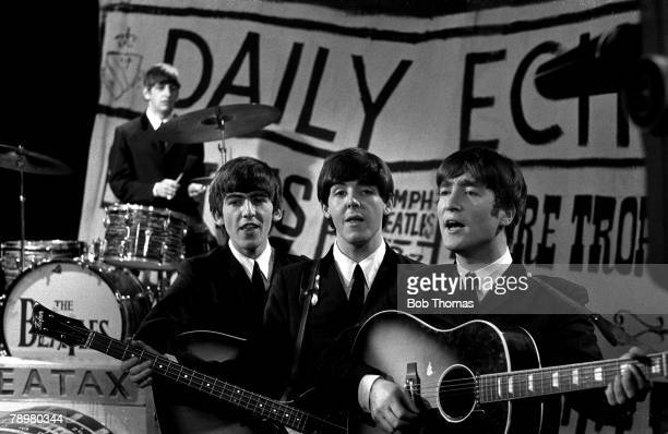 George Harrison Paul McCartney and John Lennon of 1960's Liverpool pop group The Beatles playing live on stage during a concert Ringo Starr is on...
