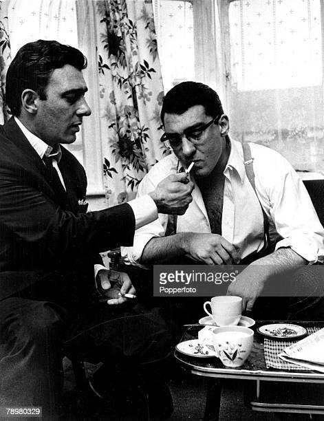 England Circa 1969 East End London gangster Reggie Kray lights up a cigarette for his twin brother Ronnie as the two relax over a cup of tea in the...