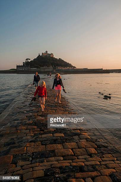 uk, england, cornwall, family on causeway at tidal island st michael's mount - st michael's mount stock pictures, royalty-free photos & images