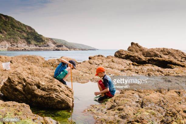uk, england, cornwall, polkerris beach, two boys fishing at the coast - cornwall england stock pictures, royalty-free photos & images