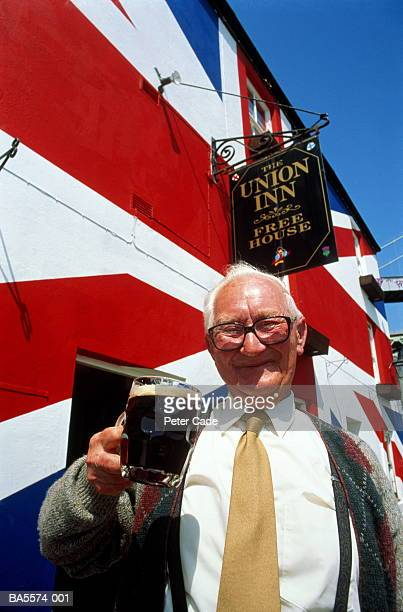 england, cornwall, saltash, man holding up pint of beer outside pub - cornish flag stock pictures, royalty-free photos & images