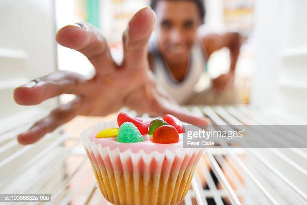 england, cornwall, young man reaching for cupcake into fridge, focus on hand - desire stock pictures, royalty-free photos & images