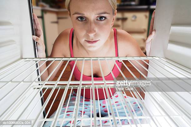 england, cornwall, young woman looking into empty fridge - hungry stock pictures, royalty-free photos & images