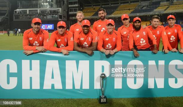 England cricket captain Eoin Morgan and team poses with the winners trophy after winning the Twenty20 International cricket match between Sri Lanka...