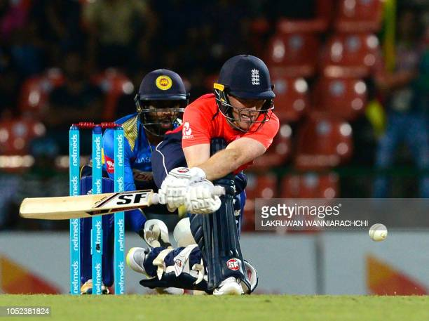 TOPSHOT England cricket captain Eoin Morgan is watched by Sri Lankan wicketkeeper Niroshan Dickwella as he plays a shot during the third one day...