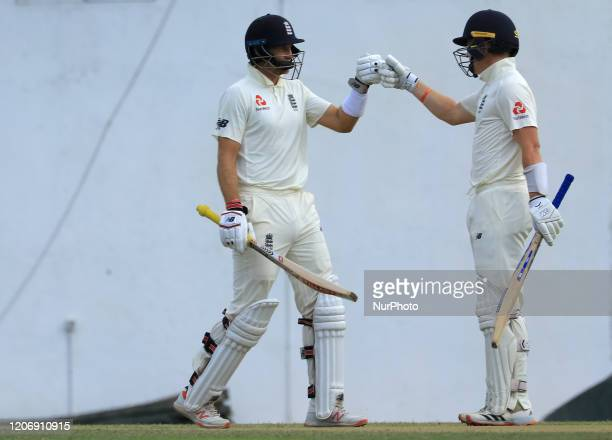 England cricket captain Joe Root celebrates after scoring 100 runs with Ollie Pope during the second day of the 2nd Warm up cricket match between Sri...
