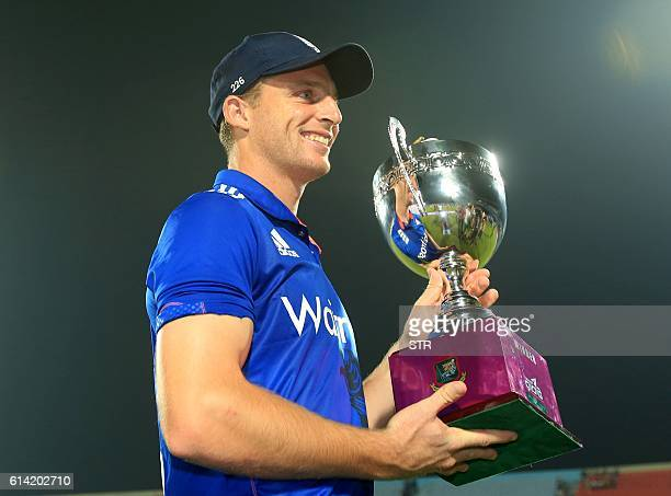England cricket captain Jos Buttler poses with the series trophy after victory in the third one day international cricket match between Bangladesh...
