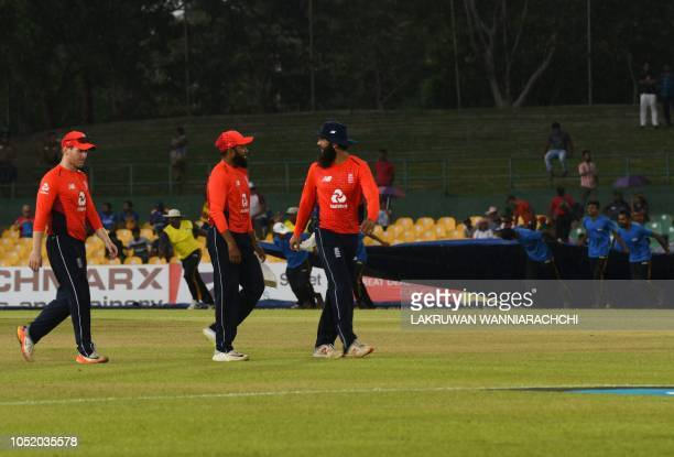 England cricket team captain Eoin Morgan Adil Rashid and Moeen Ali leave the pitch as rain starts during the second one day international cricket...