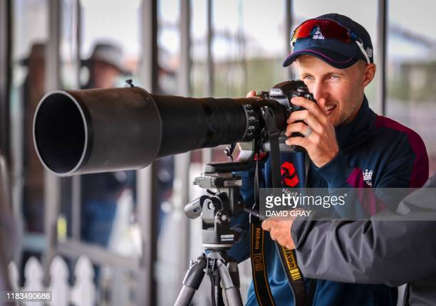 England cricket team captain Joe Root looks through a photographer's camera before a team practice session ahead of the first Test match between New...