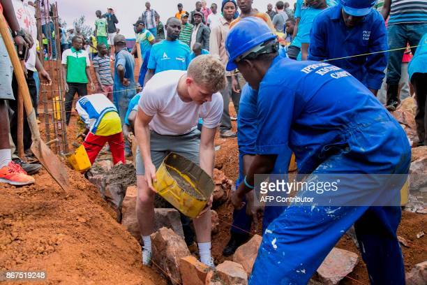 England cricket team player Sam Billings helped by a local worker pours concrete on a construction site of a secondary school in Gahanga district in...