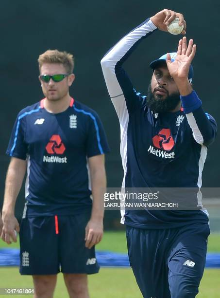 England cricketer Adil Rashid delivers a ball as Liam Dawson looks on during a practice session at the Rangiri Dambulla International Cricket Stadium...