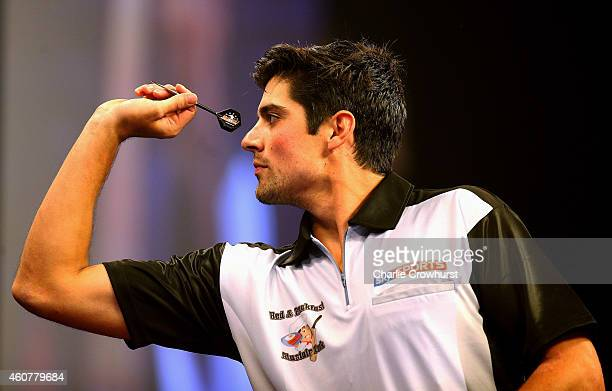 England cricketer Alastair Cook plays a leg of darts against James Anderson ahead of the William Hill PDC World Darts Championships on Day Five at...