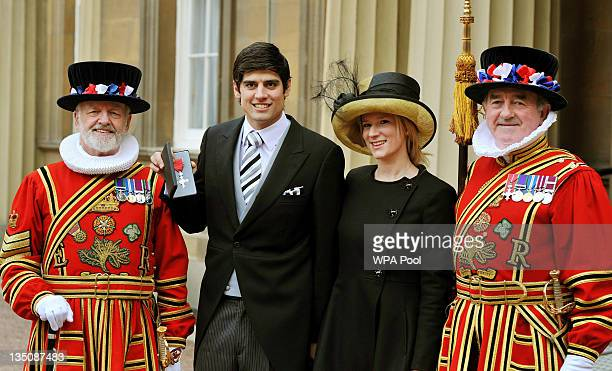 England cricketer Alastair Cook poses with his fiancee Alice Hunt and members of the Queen's bodyguard of Yeoman of the Guard after being made an MBE...