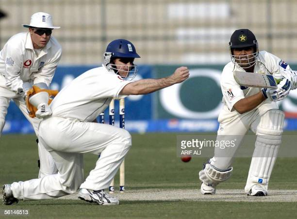 England cricketer Ashley Giles tries to catch a ball hit by Pakistani batsman Kamran Akmal during the opening day of first Test match in Multan...